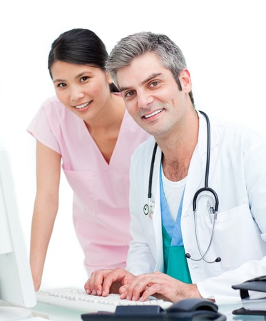 Smiling doctor and nurse working at computer photo