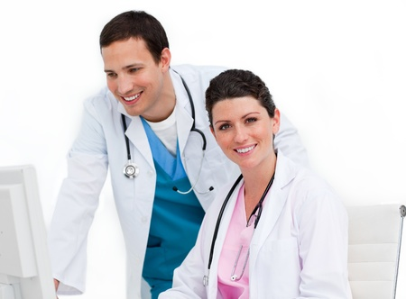 Male doctor and nurse working at computer photo
