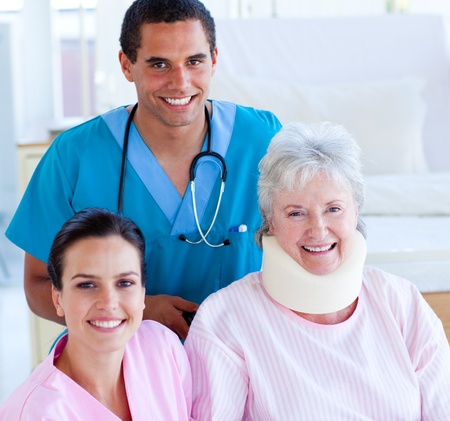more mature: Two smiling doctors taking care of an injured senior woman Stock Photo