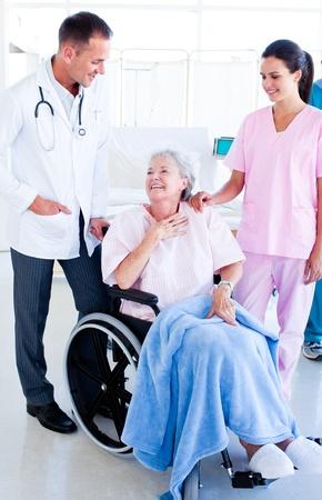 equipe medica: Sorridente equipe medica di prendersi cura di una donna senior Archivio Fotografico