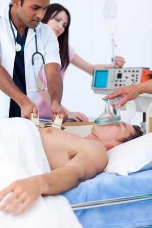 defibrillator: Serious medical team resuscitating a patient