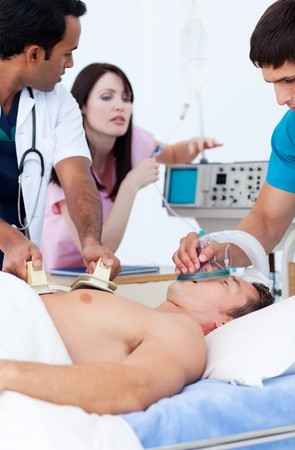defibrillator: Ambitious medical team resuscitating a patient Stock Photo