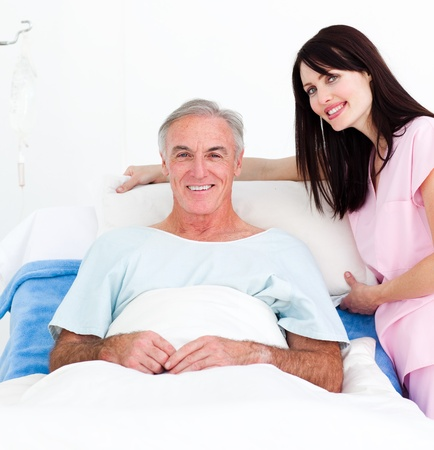 Smiling nurse fixing a senior patients bed  photo