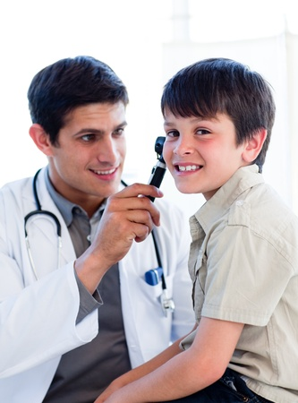 Charming doctor examining little boys ears photo