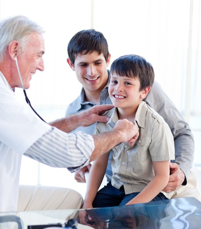 Positive doctor examining a little boy with his father photo