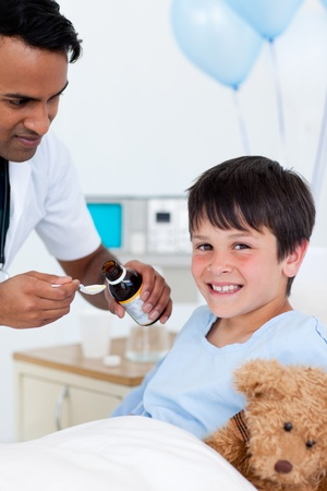 Positive doctor giving medicine to a little boy photo