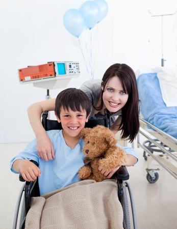 Smiling little boy sitting on wheelchair and his mother photo