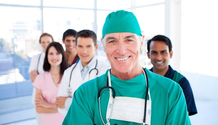 assertive: Assertive senior surgeon standing with his colleagues