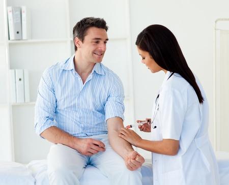 Un médico dando una inyección de un paciente varón Foto de archivo - 10259329