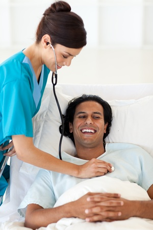 A doctor checking the pulse of a smiling patient photo