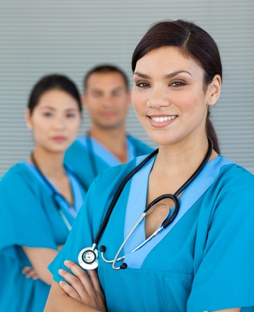 surgical scrubs: Attractive female doctor with his colleagues in the background