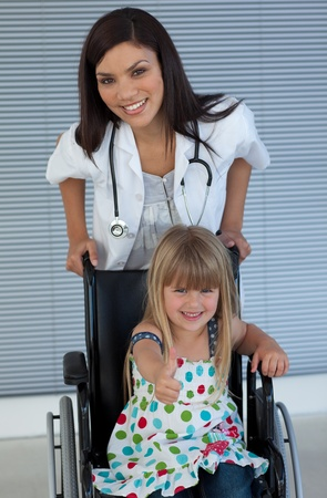 Young female doctor and Smiling girl on a wheelchair with thumb up photo