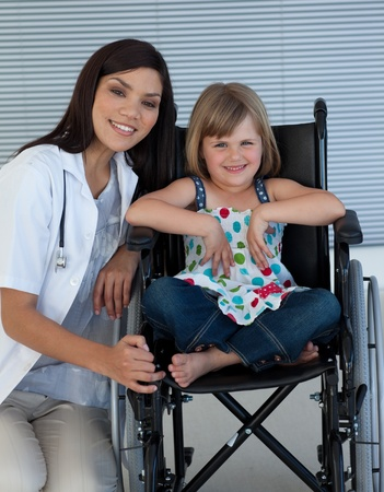Cute girl sitting on a wheelchair with a female doctor photo