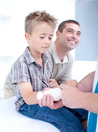 Bandaging an arm injury on a child photo