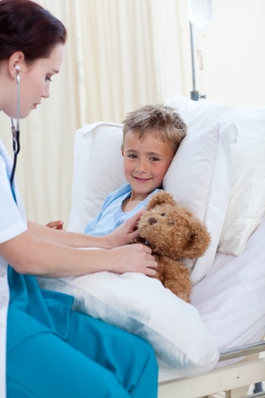 Female doctor listening to a child chest and a teddy bear photo