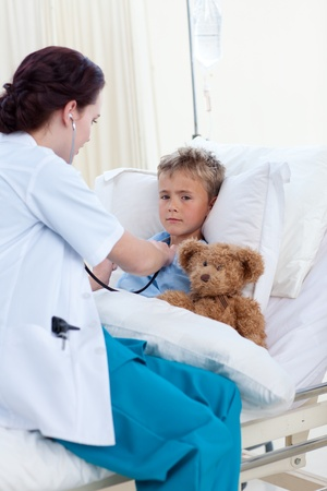 Female doctor listening to a child chest with stethoscope photo
