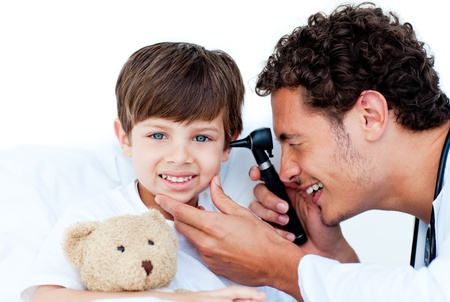 Smiling doctor examining patients ears photo