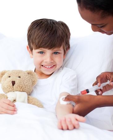 백신: 주사를 받고 웃는 어린 소년 스톡 사진