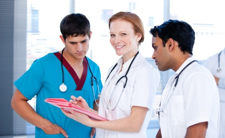 Cheerful female doctor working with her team photo