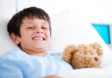 sick teddy bear: Smiling little boy lying in a hospital bed