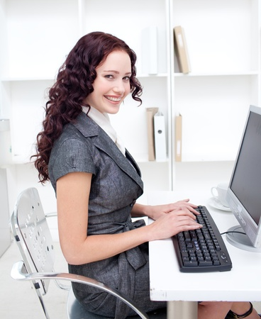 Smiling businesswoman working in office with a computer Stock Photo - 10258358