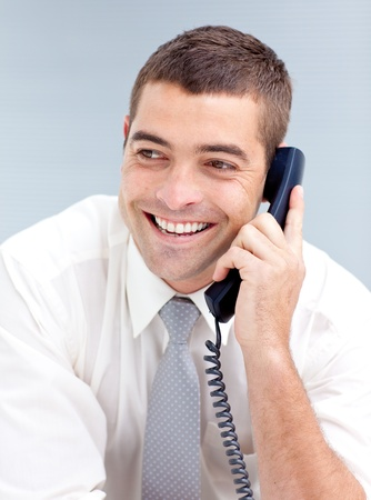 conference call: Smiling businessman in office talking on phone