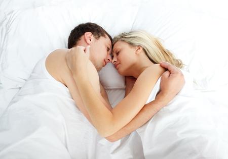 cuddling: Boyfriend looking at her girlfriend sleeping in bed Stock Photo