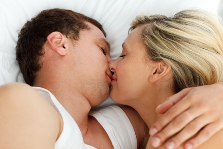 Amorous couple kissing in bed photo