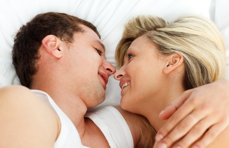 Lovers looking each other in bed photo