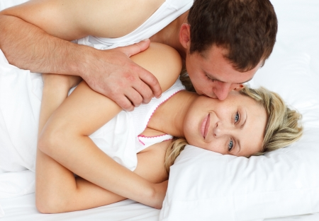 Boyfriend kissing his girlfriend in bed Stock Photo - 10255577