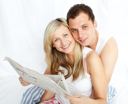 Couple reading a newspaper in bed and smiling at the camera photo