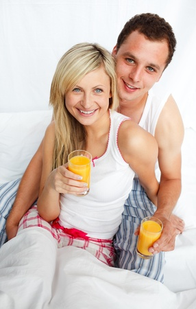 Couple holding orange juice glasses in bed photo