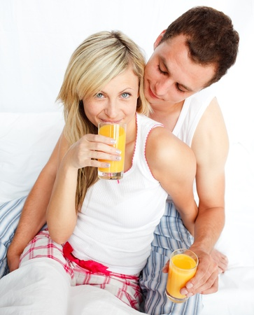 Couple drinking orange juice in bed photo
