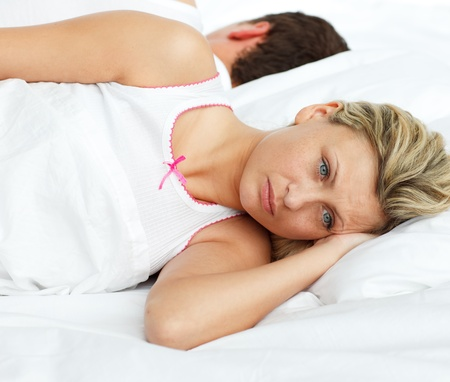 Upset woman in bed sleeping separate of a man photo