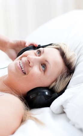 Charming woman with headphones on lying on a bed photo