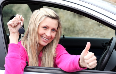 woman driving car: Jolly female driver showing a key after bying a new car