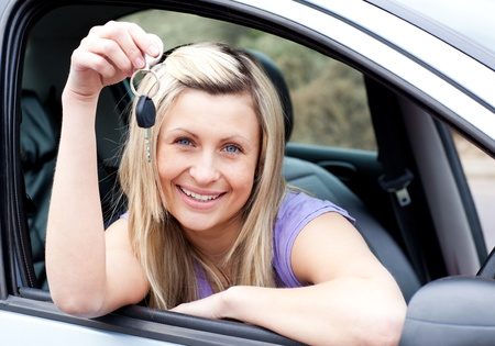 driving school: Happy young driver holding a key after bying a new car