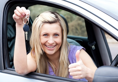 driving school: Charming female driver showing a key after bying a new car  Stock Photo