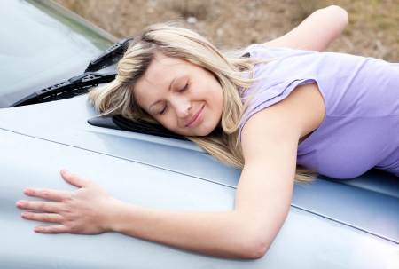 new motor vehicles: Cheerful female driver huging her new car  Stock Photo