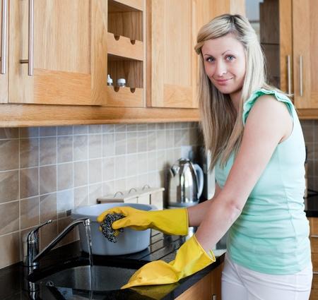 clean home: Lachende jonge vrouw het schoonmaken in een keuken Stockfoto