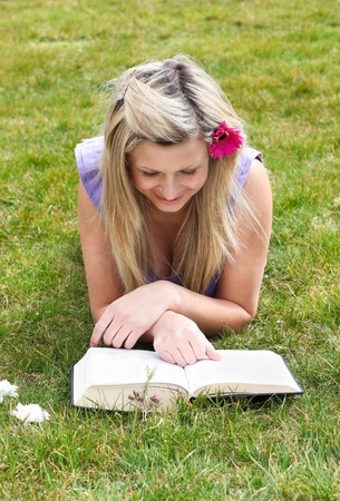 Young woman reading a book in a park  photo