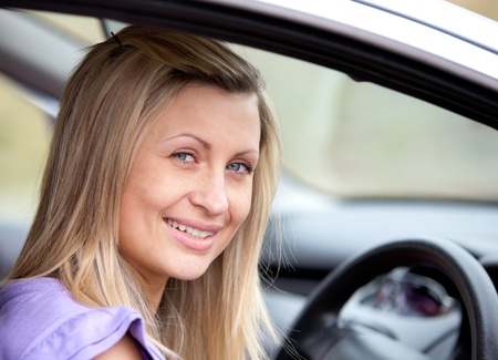 Jolly young female driver sitting in her car photo