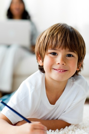 Smiling little boy drawing lying on the floor  photo