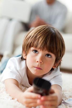 Concentrated little boy watching TV lying on the floor  photo