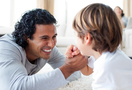Cheerful father and his son armwrestling Stock Photo - 10245160