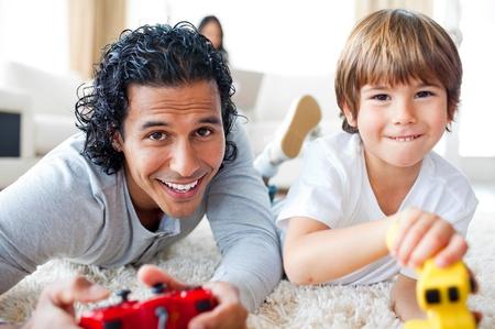 playing video games: Padre alegre y su hijo jugando juegos de video en el suelo