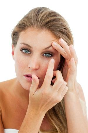 Beautiful woman putting a contact lens photo