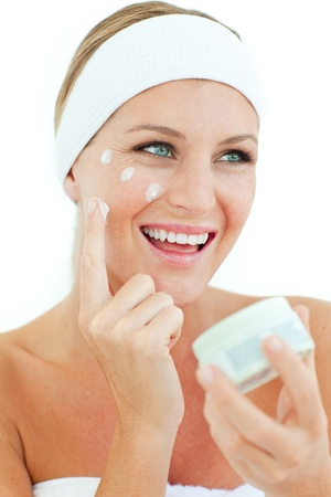 Jolly woman putting cosmetic cream photo
