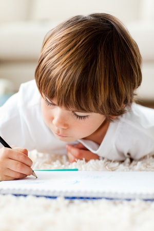 Serious little boy drawing lying on the floor photo