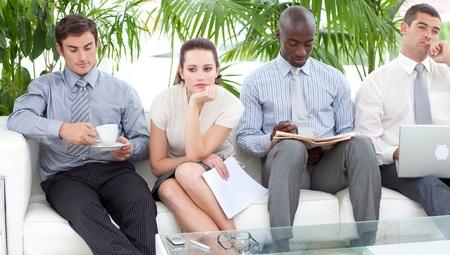 bored face: Bored business people sitting on a sofa waiting for an interview Stock Photo